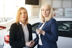 Auto business, car sale, consumerism and people concept - happy woman with car dealer in auto show or salon royalty free stock image