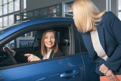 Auto business, car sale, consumerism and people concept - happy woman with car dealer in auto show or salon. Auto business, car sale, consumerism and people Royalty Free Stock Photo