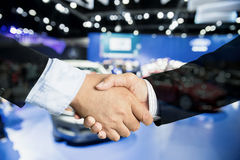 Auto business, car sale, deal, gesture and people concept - Clos. E up of male handshake in auto show or salon Royalty Free Stock Photo