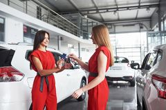 Auto business, car sale, deal, gesture and people concept - close up of dealer giving key to new owner in auto show or. Salon Stock Photo