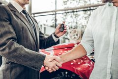 Close up view of dealer giving key to new owner and shaking hands in auto show or salon royalty free stock photography