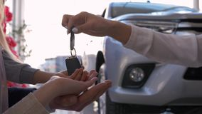 Auto business, family hands of owners car take keys on background of automobile close-up in sales center