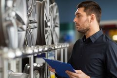Auto business owner and wheel rims at car service Stock Image
