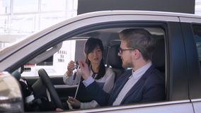 Auto business, successful asian woman car seller advises to guy buyer sitting inside automobile gives keys and shakes. Auto business, successful asian woman car stock video footage