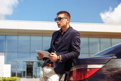 Auto business, transport, leisure and people concept - happy handsome man near car with tablet. Transport, business trip, technology and people concept - close Stock Photo