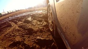 Auto car goes through puddles and mud sun glare on stock video footage