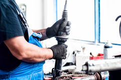 Auto car mechanic adjusting a car shock absorber Royalty Free Stock Images