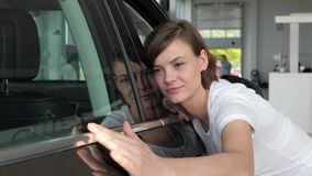 Auto center, Portrait female client, lucky customer inspecting her new. Automobile color, young woman customer stands next to auto, admiration from novel stock video footage