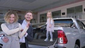 Auto compra da família, par alegre com dança engraçada da menina da criança com chaves ao comprar o automóvel novo no carro video estoque