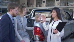 A auto compra feliz, vendedor do carro consulta a família feliz dos compradores com pouca filha no tronco do automóvel no centro  video estoque