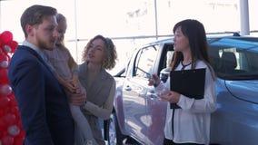 A auto compra, pares novos com criança compra o automóvel e a fêmea asiática do vendedor dá chaves das mãos na sala de exposições video estoque