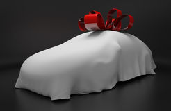 Auto concept of a new covered sports car topped with a red ribbon as a gift. Auto concept of a new sports car covered in a white sheet and topped with a red Royalty Free Stock Images