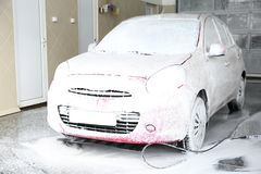 Auto covered with foam at car wash stock images