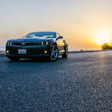Auto Curves. The sexy curves of the Chevrolet Camaro SS, with the sea and sunset in the background and a road in the front Stock Images