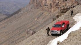 Auto, das auf Gebirgsstraße in einem trockenen, desertic, Landschaft, nahe Abgrund reist stock footage