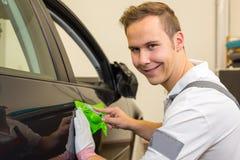 Auto, das den Spezialisten schneidet Klebefolie oder Film mit einem Kastenschneider einwickelt Lizenzfreie Stockbilder