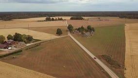 Auto, das Landschaftslandstraße unter Getreideweizenfeldern und Bauernhäusern weitergeht stock footage