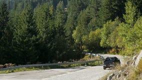 Auto, das leere Straße in den Bergen, dichten Wald wächst auf den Steigungen, ruhig hinuntergeht stock video