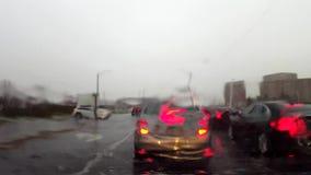 Auto, das in Verkehr beim Regnen auf Windschutzscheibe wartet Fahrzeug, das auf Stadt-Straße vom Fahrer-Gesichtspunkt POV leerläu stock footage