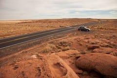 Auto, das Wüstenlandstraße abstellt lizenzfreie stockfotos