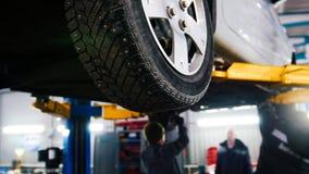 Auto in de autodienst die voor het herstellen, werktuigkundigen in garage opheffen Royalty-vrije Stock Foto's