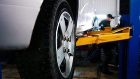 Auto in de autodienst die voor het herstellen, werktuigkundigen in garage opheffen Royalty-vrije Stock Foto
