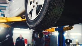 Auto in de autodienst die voor het herstellen, werktuigkundigen in garage opheffen Stock Foto's