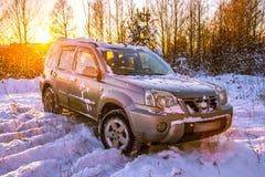 Auto in de winterzonsondergang stock fotografie