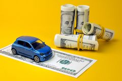 Auto dealership and rental car. Concept of insurance, credit and car purchases, leasing, car loan,  Auto dealership and rental, new car buy. toy car dollar bill stock image