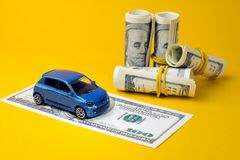 Auto dealership and rental. Concept of insurance, credit and car purchases, leasing, car loan,  Auto dealership and rental, new car buy. toy car dollar bill royalty free stock image