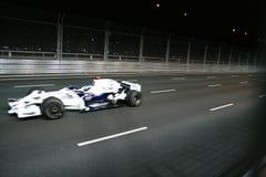 Auto der Formel 1, das am Nachtrennen beschleunigt. Lizenzfreies Stockbild