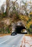 Auto in der Straße, die vom Tunnel in den Bergen fährt, in geblutet stockfotos