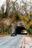 Auto in der Straße, die vom Tunnel in den Bergen geblutet fährt stockbild