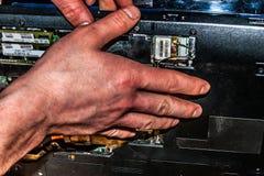 Auto-desmontagem de um portátil, eletrônica, reparo do portátil, mãos masculinas imagens de stock