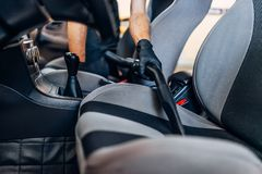 Auto detailing, cleaning seats with vacuum cleaner. Auto detailing of car interior on carwash service. Worker in gloves cleaning seats with vacuum cleaner royalty free stock photos