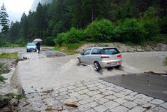 Auto die een overstroomde weg kruist Stock Foto's
