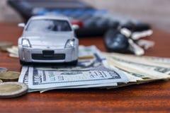 Auto die op bankbiljetten, en zich naast een stuiver en autosleutels bevinden Stock Fotografie