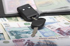 Auto documents and a car key. Black wallet with autodocuments and a car key on denominations Stock Image