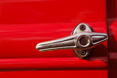 Auto door lever. Close-up of a door lever on a red vintage car Stock Photos