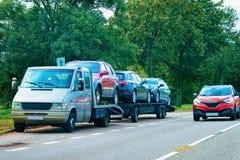 Auto dragende aanhangwagen met nieuwe voertuigen op asfaltweg, Slovenië royalty-vrije stock fotografie