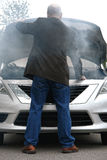 Auto Driver and Open Car Engine Hood in Fire Smoke. Auto driver standing in front of a broken down car open engine compartment hood with smoke from an automotive Stock Image