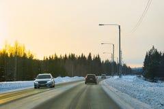 Auto in een weg bij de sneeuwzonsondergang van de winterlapland royalty-vrije stock foto's