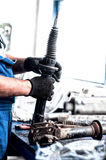 Auto engineer mechanic working on car shock absorber. In car service workshop Royalty Free Stock Image