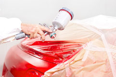Auto engineer painting a red paint on car Royalty Free Stock Images