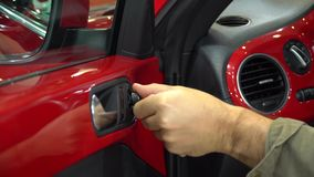Auto exhibition Man testing a red car and its side mirror and window button dashboard inside the car. stock video