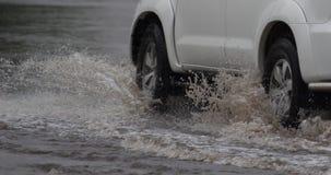 Auto fährt in starken Regen auf eine überschwemmte Straße Lizenzfreies Stockfoto