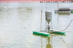 Auto feeder machine floating on the aquaculture pond. Autometic feeder or Auto feed at earthen pond in Aquaculture farm.  stock photography