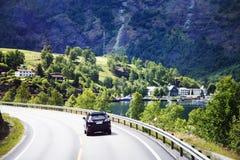 Auto gå på en vägspolning mellan berg Arkivbild
