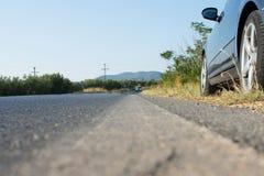 Auto geparkt durch die Seite einer Straße im ländlichen Land Hinterhalt durch schwarzes Auto auf Asphalt Road Lizenzfreie Stockfotos