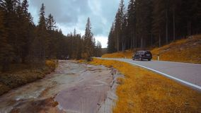 Auto gibt die Straße mitten in dem Holz mit einem Fluss längsseits weiter stock footage